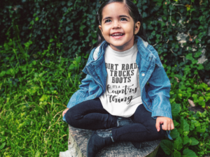 little-girl-wearing-a-denim-jacket-and-t-shirt-mockup-in-the-garden-a12098